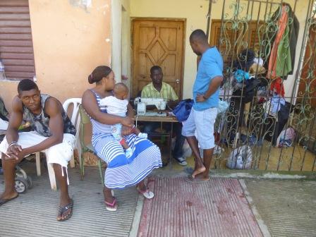 Celui-là, c'est devant sa porte qu'il a décidé de réparer jupes et pantalons, entouré tandis que celui-là, entouré de sa nombreuse famille